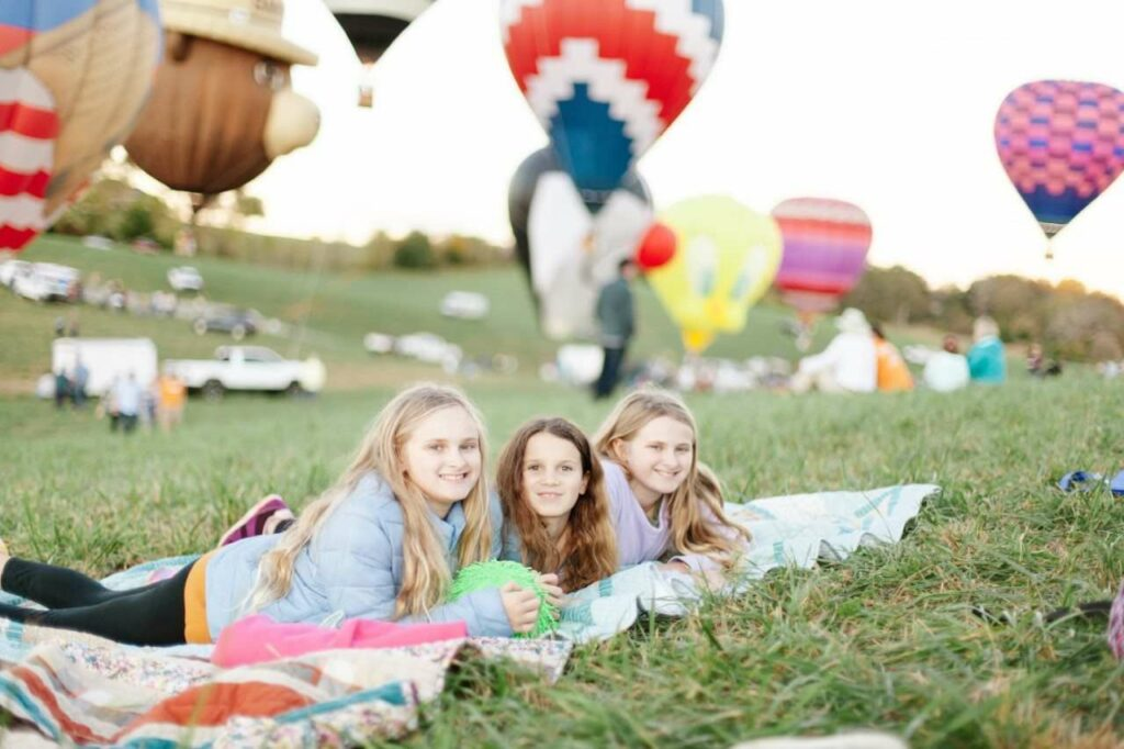 three young women sitting on a blanket at lakeside of the smokies balloonfest
